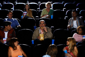 Mature Man Eating Potato Chips in Movie Theater Auditorium