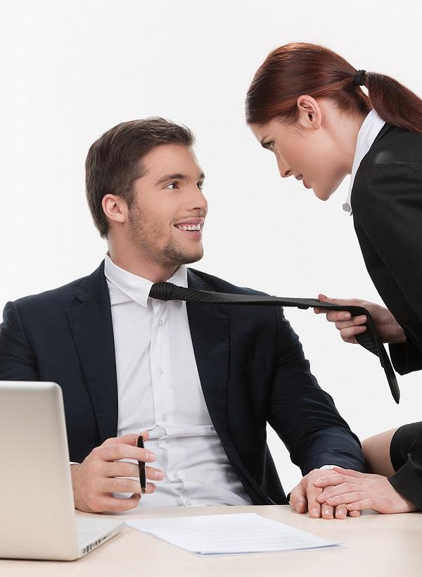 beautiful woman pulling man by tie.